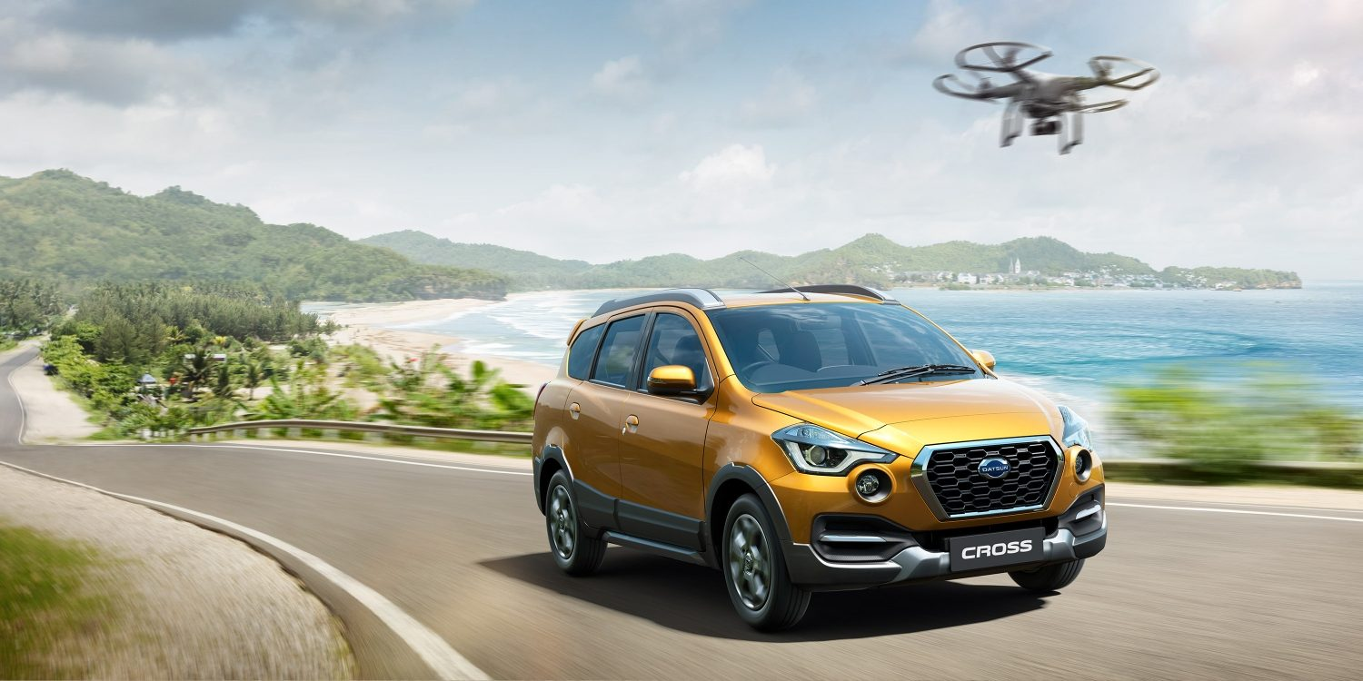 Datsun Cross traveling on seaside road with drone device flying by