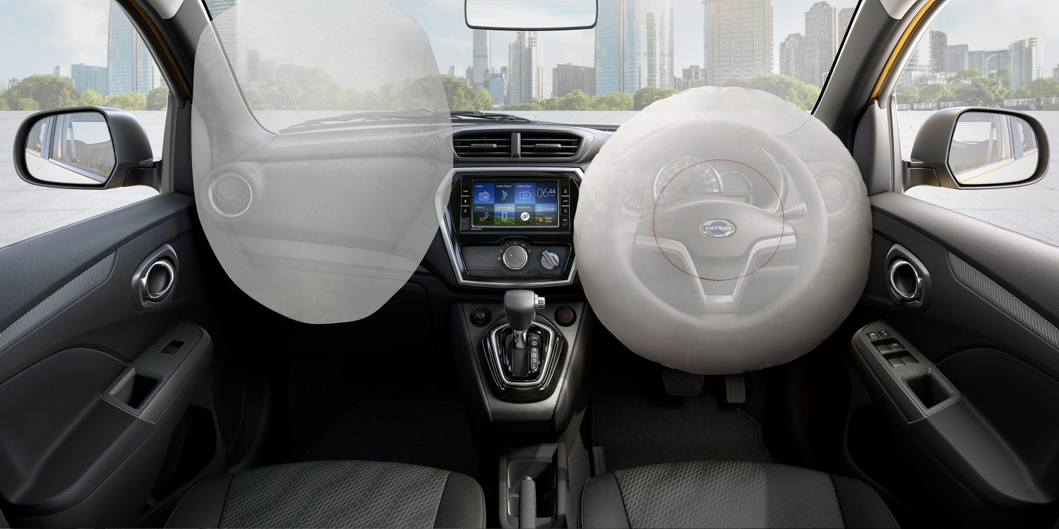 Datsun Cross interior with airbags deployed and city scape visible through windows