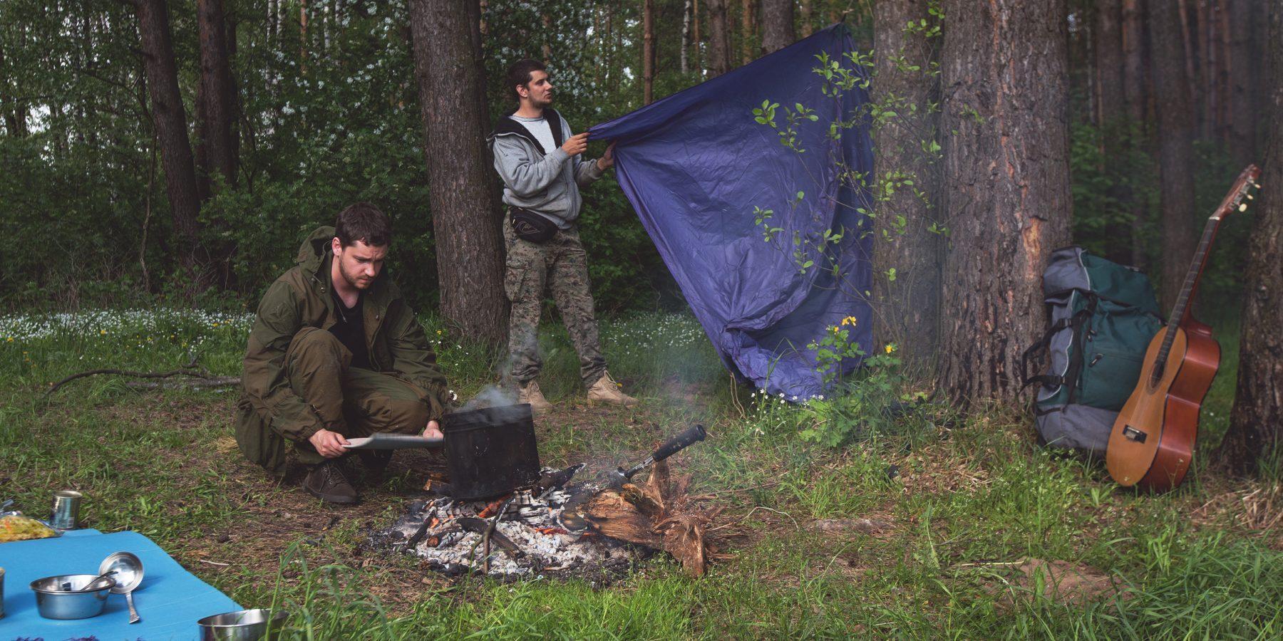 Друзья раскидывают походный лагерь влесу.
