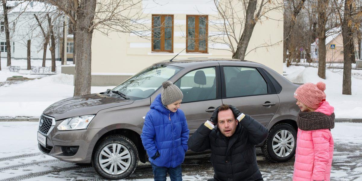 Папа идети около автомобиля Datsun