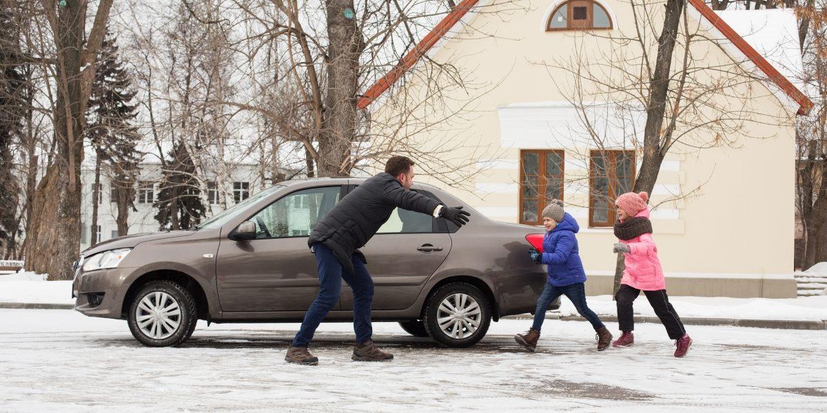 Отец идети около автомобиля Datsun