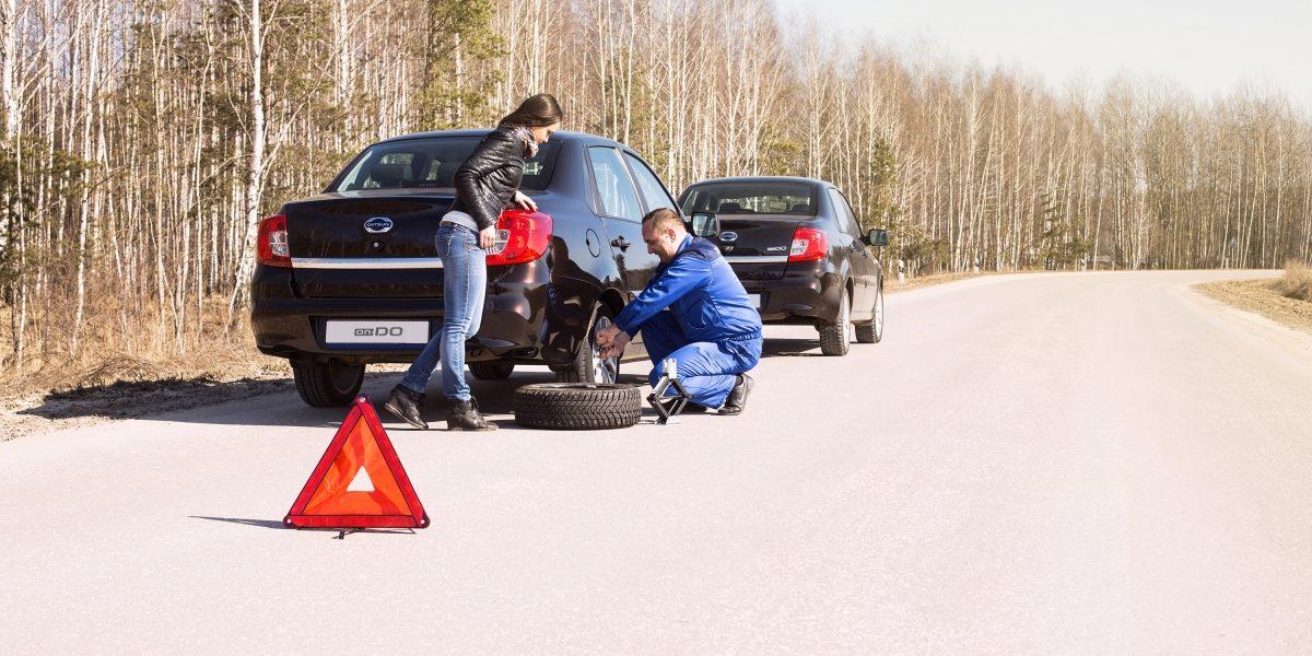 """Специалист сервиса """"Помощь надорогах"""" Datsun меняет колесо наавтомобиле Datsun"""